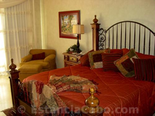 master suite with attractive bedding also features maple furniture and seating.
